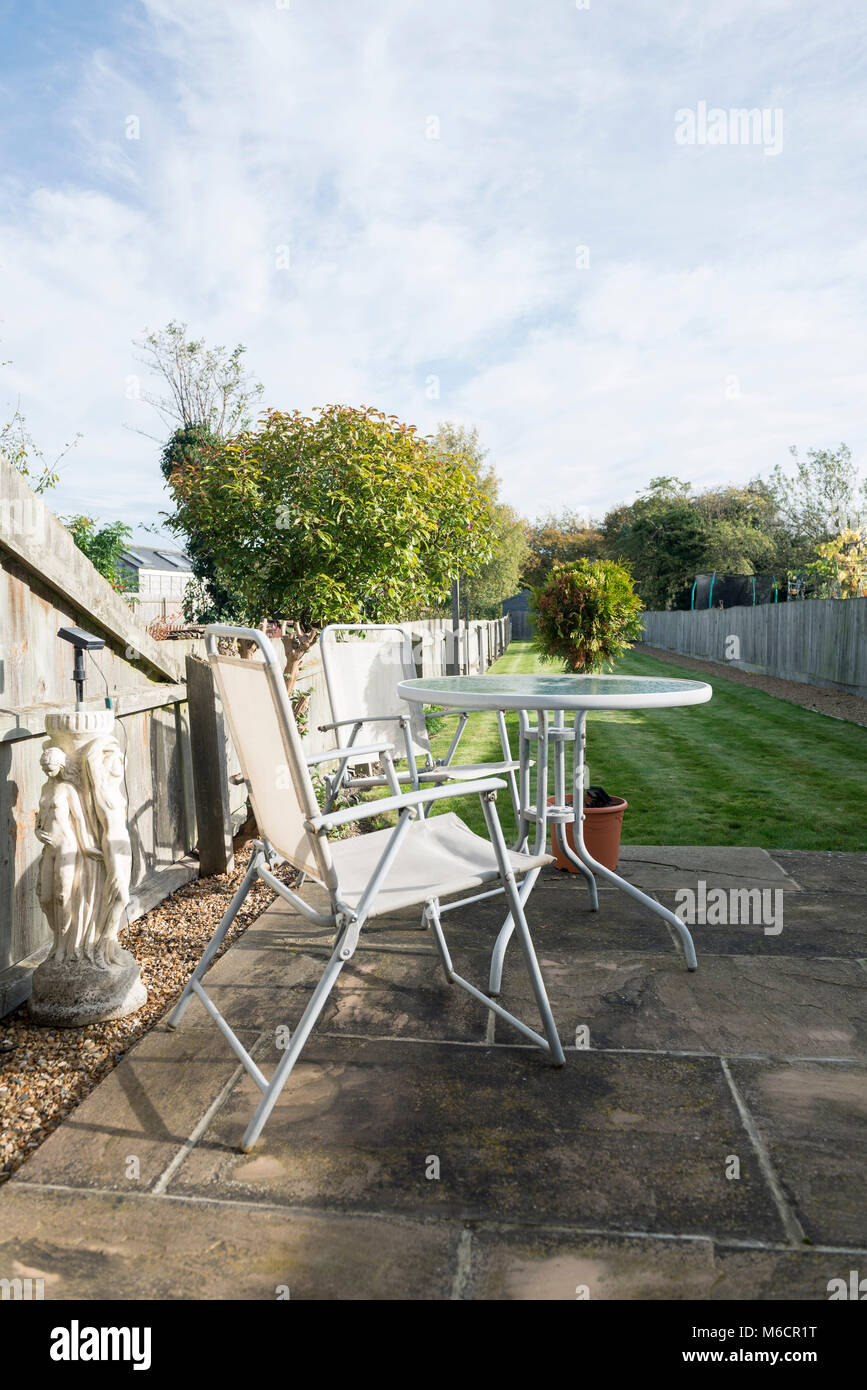a typically british suburban garden with a patio, lawn, table and chairs Stock Photo