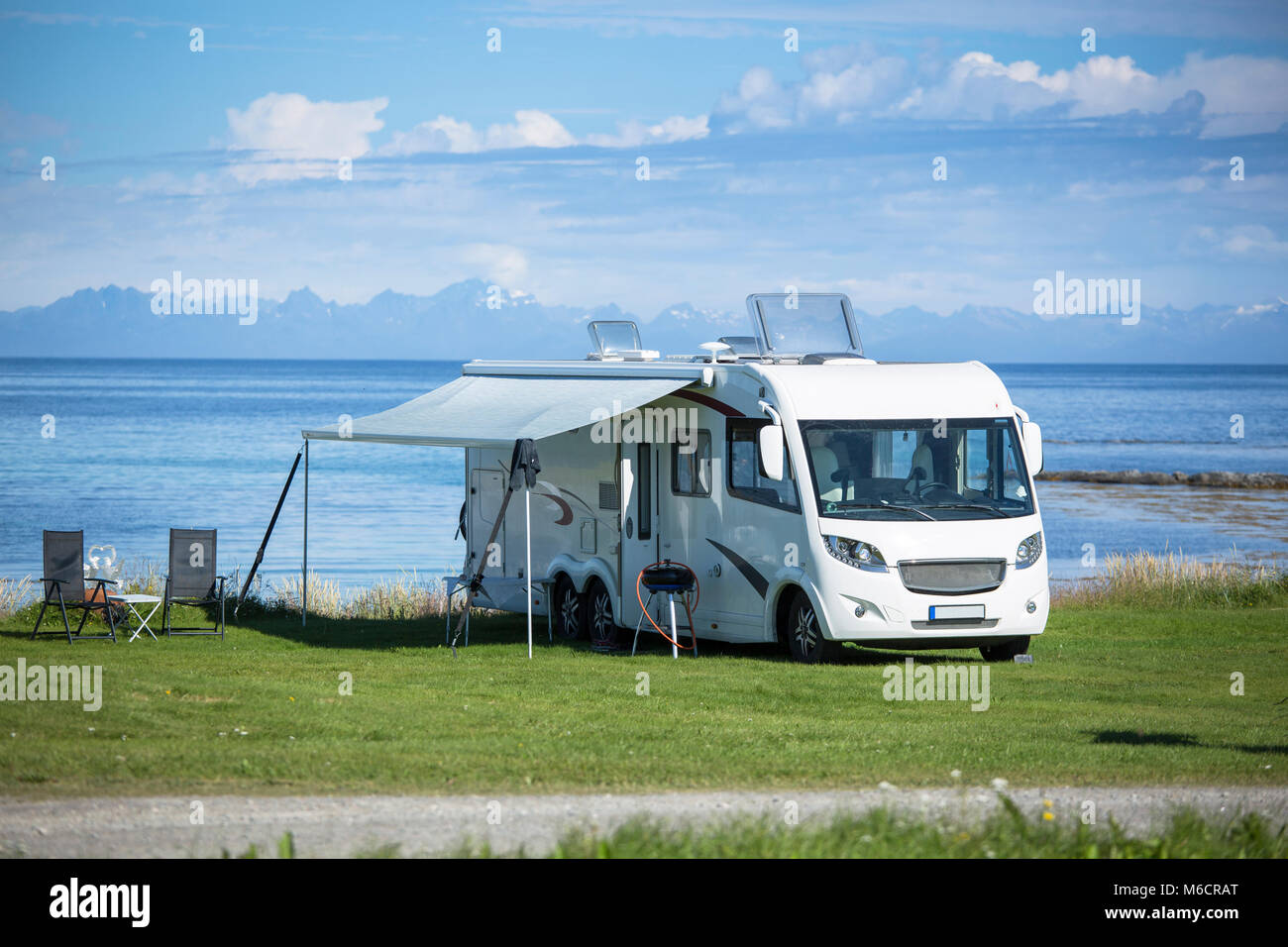 Motorhome parking nearby the water at Engeloya, Norway. The wall of Lofoten Oslands is rising in the horizon. - Stock Image