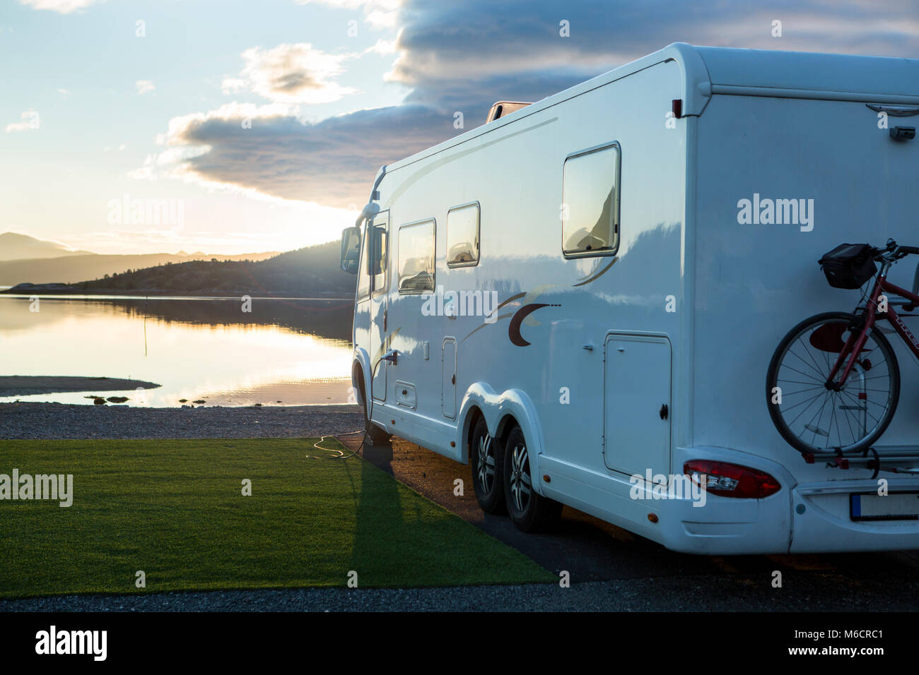 Large camper Van parking near the water at a campsite for motorhomes. Its sunset and the water is calm. - Stock Image