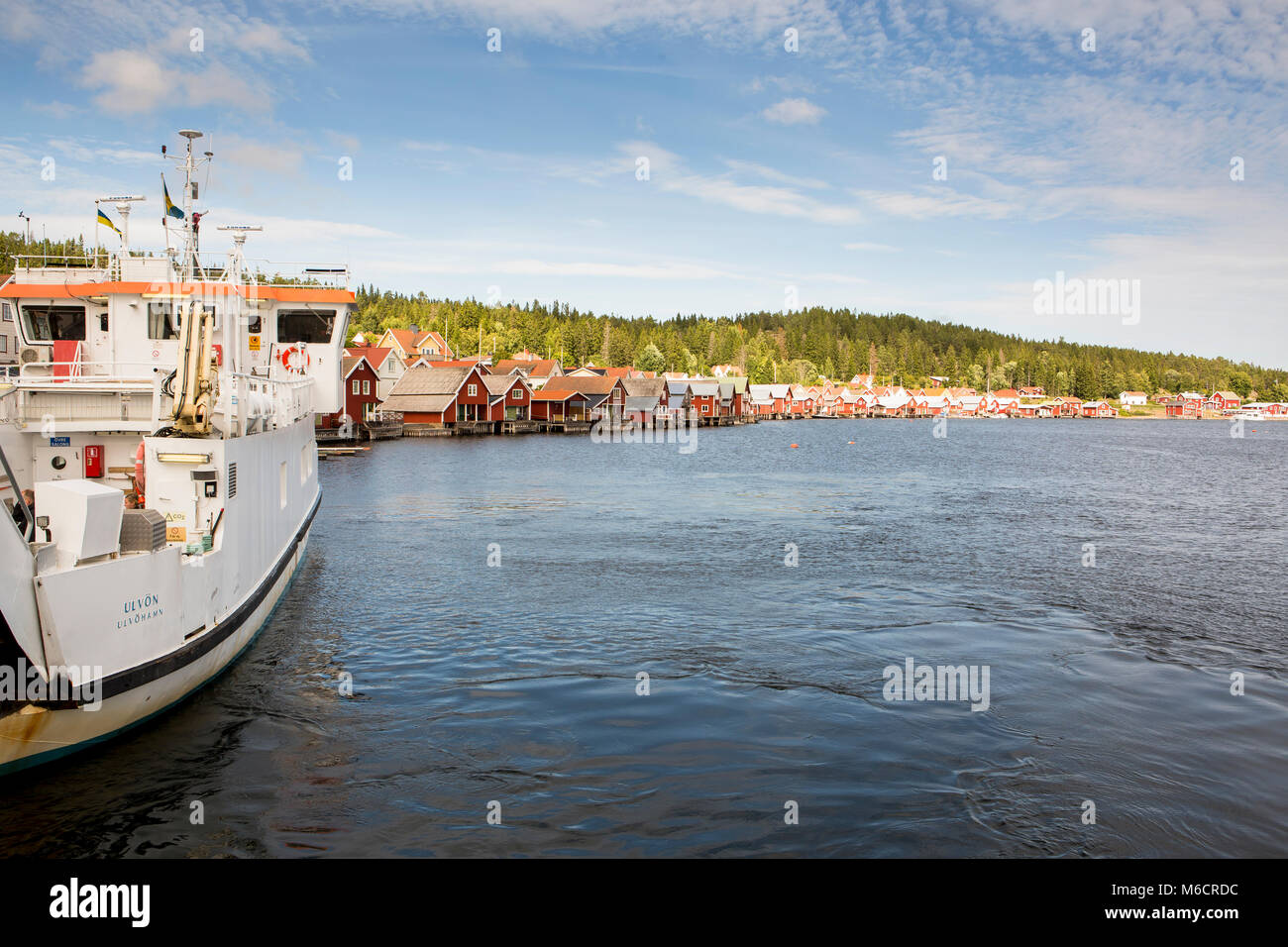 The harbour of Ulvon, Sweden, where small, red wooden houses are built at the waterline. - Stock Image