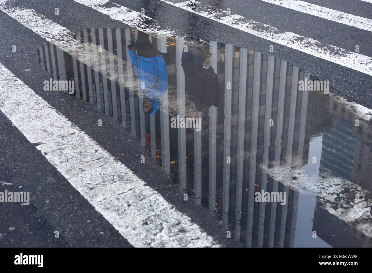 Reflection of the General Motors building in a puddle on New York's Fifth Avenue Stock Photo