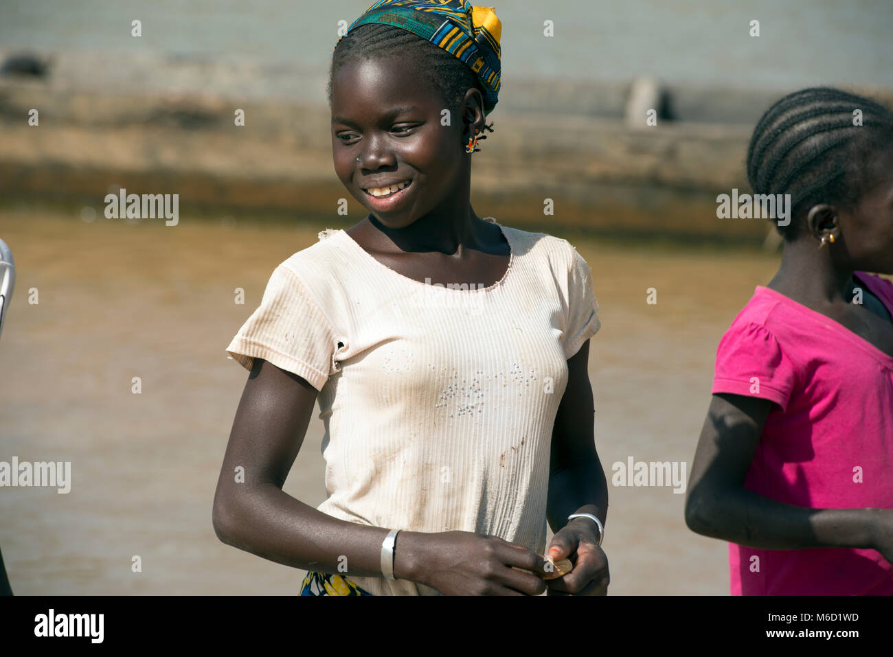 A young, indigenous, ethnic teenaged Bozo tribal girl, smiling, wearing a t-shirt. Mali, West Africa. - Stock Image
