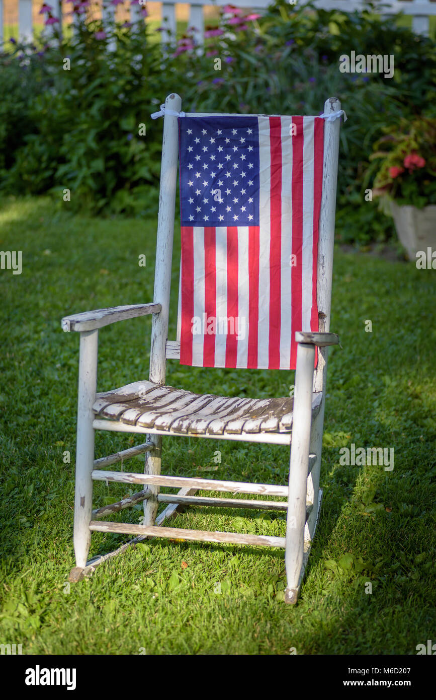 Rustic Old White Painted Rocking Chair Sitting In Backyard With American  Flag Draped Over The Back