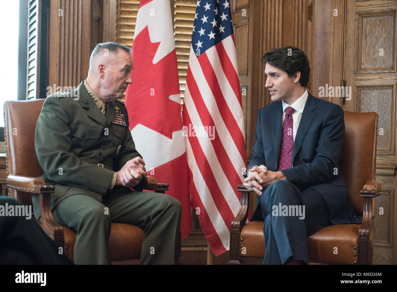 U.S. Marine Corps Gen. Joe Dunford, chairman of the Joint Chiefs of Staff,  speaks with Justin Trudeau, Prime Minister of Canada,  in the Canadian Parliament buildings, Ottawa, Canada, Feb. 28, 2018. Gen. Dunford was in Ottawa for meetings with senior Canadian officials on the ongoing evolution of the North American Aerospace Defense Command. (DoD Photo by U.S. Army Sgt. James K. McCann) Stock Photo