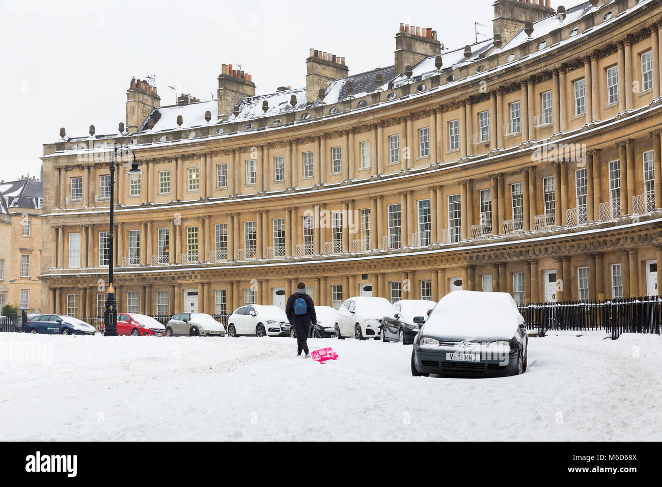 BATH, UK - MARCH 2, 2018 :  A woman drags a sled along the road in snowy conditions at the Circus, a Georgian terraced Stock Photo