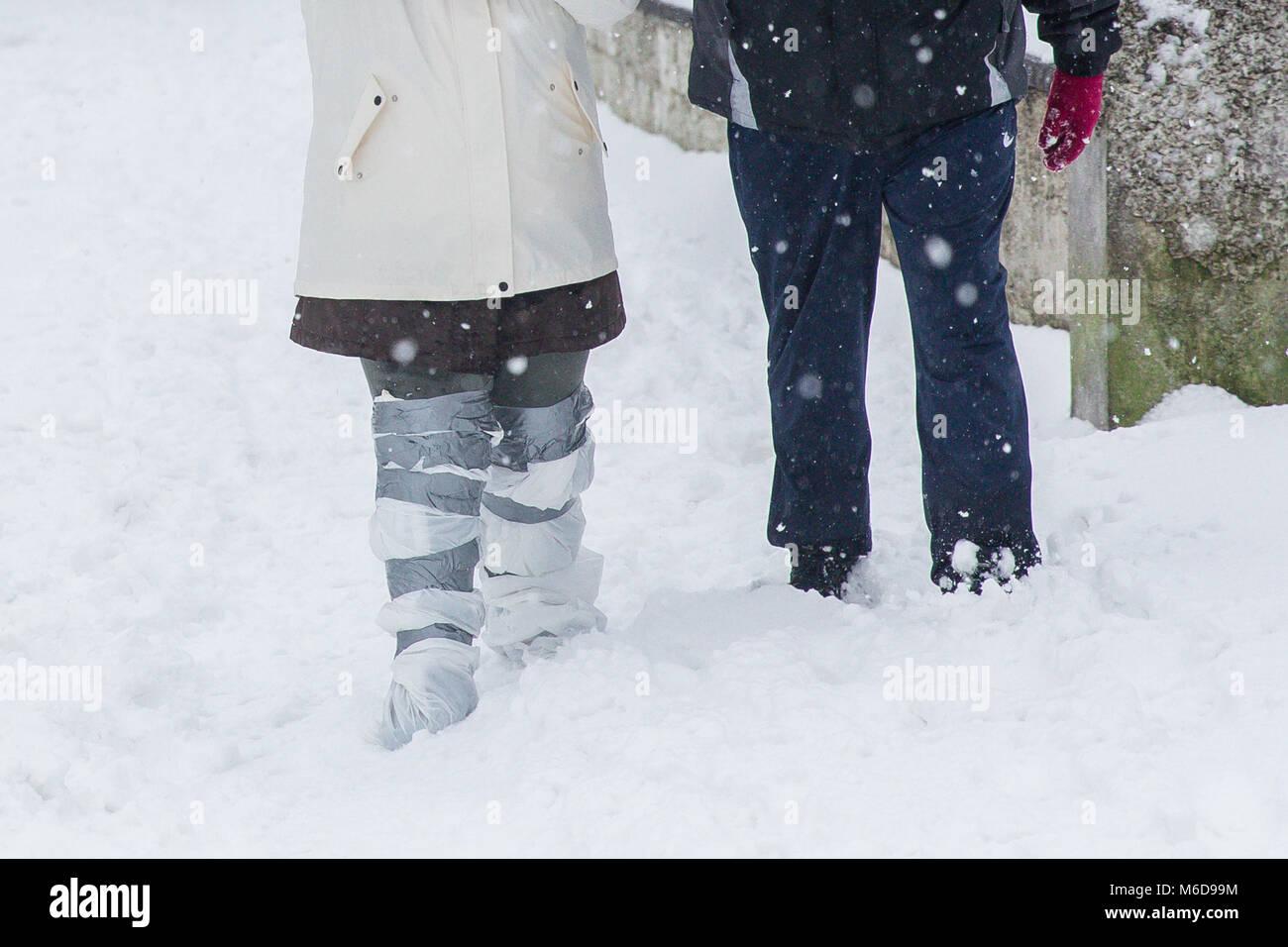 Celbridge, Kildare, Ireland. 02 Mar 2018: Couple out walking through the snow with plastic bags wrapped around legs - Stock Image