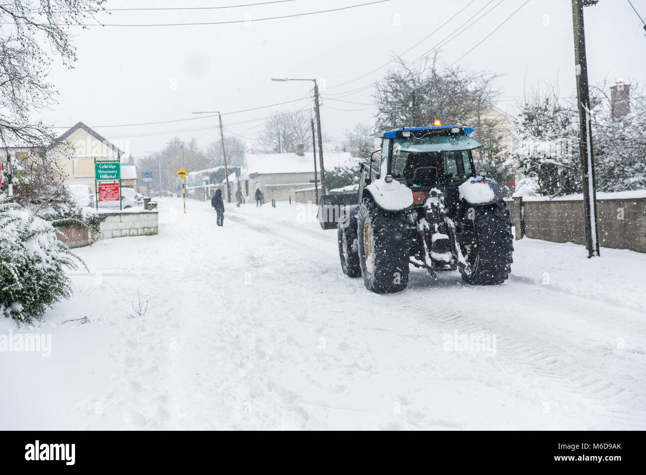 Celbridge, Kildare, Ireland. 02 Mar 2018: Tractor with front loader driving through covered in snow Celbridge. Local - Stock Image