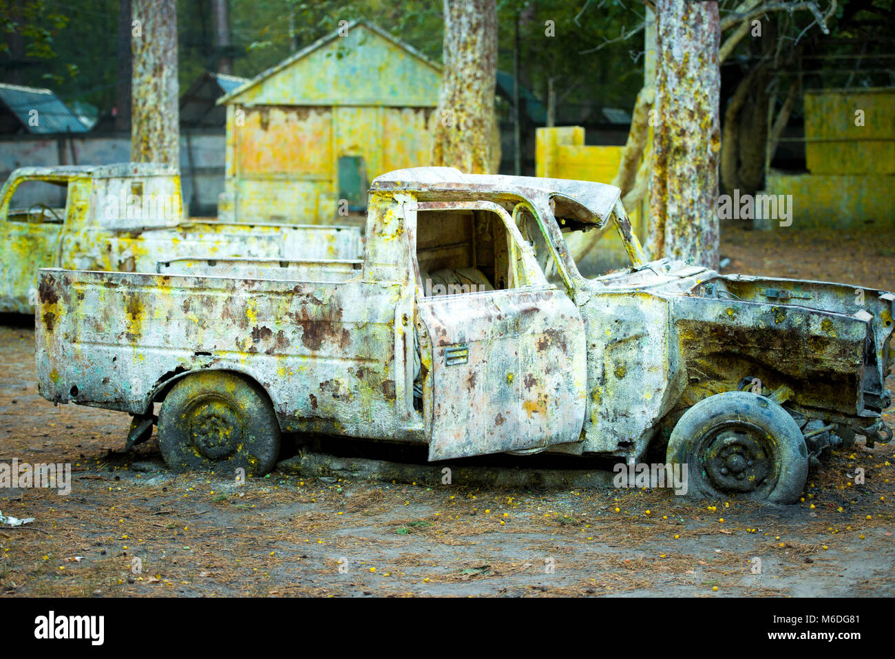 An old rusty car in paint from paintball. - Stock Image