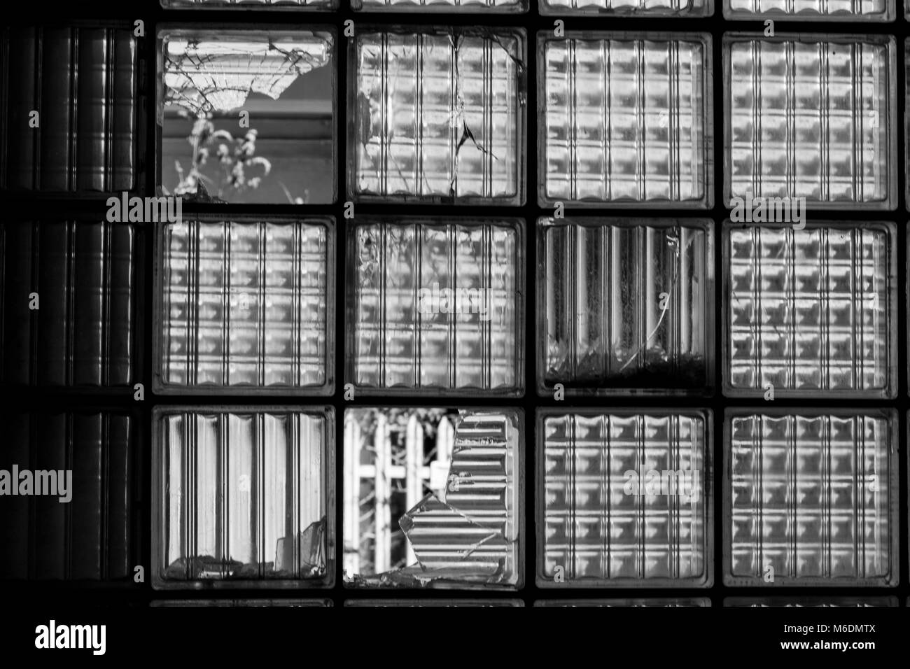Black and White Detail of a Thick, Frosted Window in a Derelict Factory; Great Torrington, Devon, England. - Stock Image