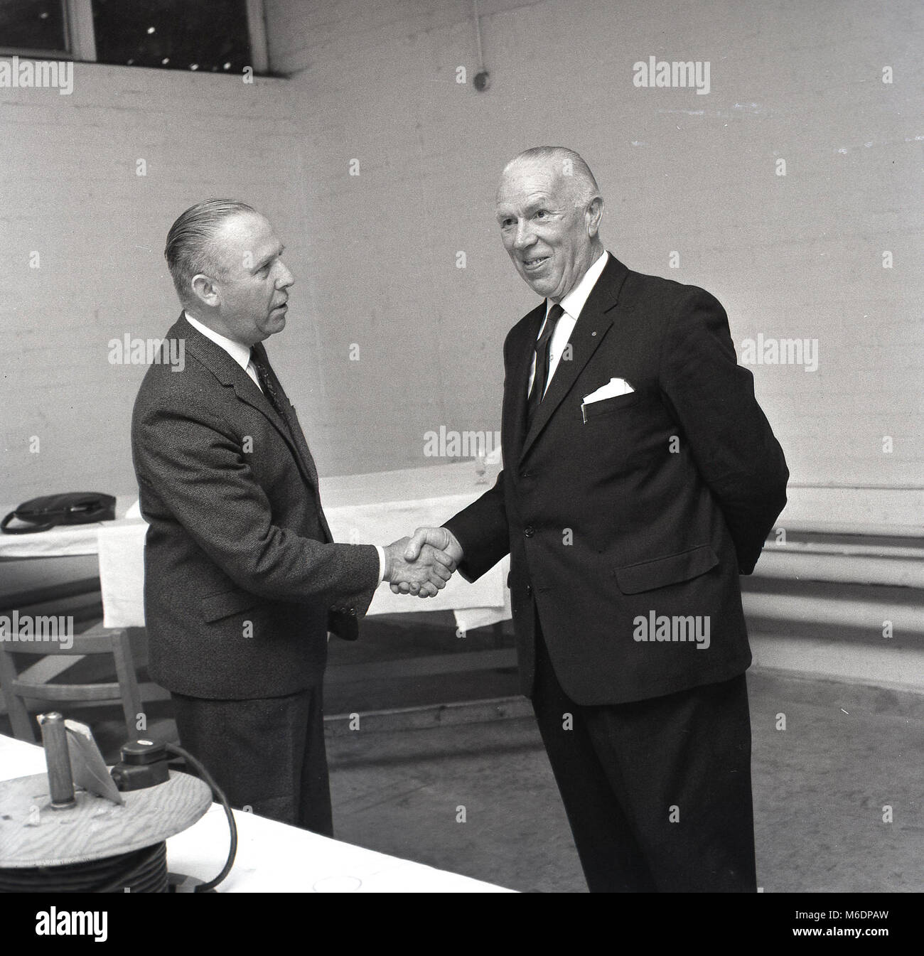 1960s, England, UK, picture shows two well-dressed men wearing suits standing up shaking hands. A firm handshake Stock Photo