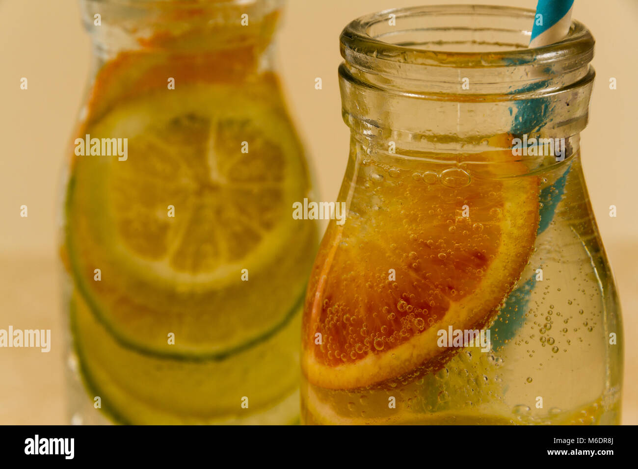 Children's sparkling water drinks in bottles with straw. Slices of orange, lemon and lime. Stock Photo