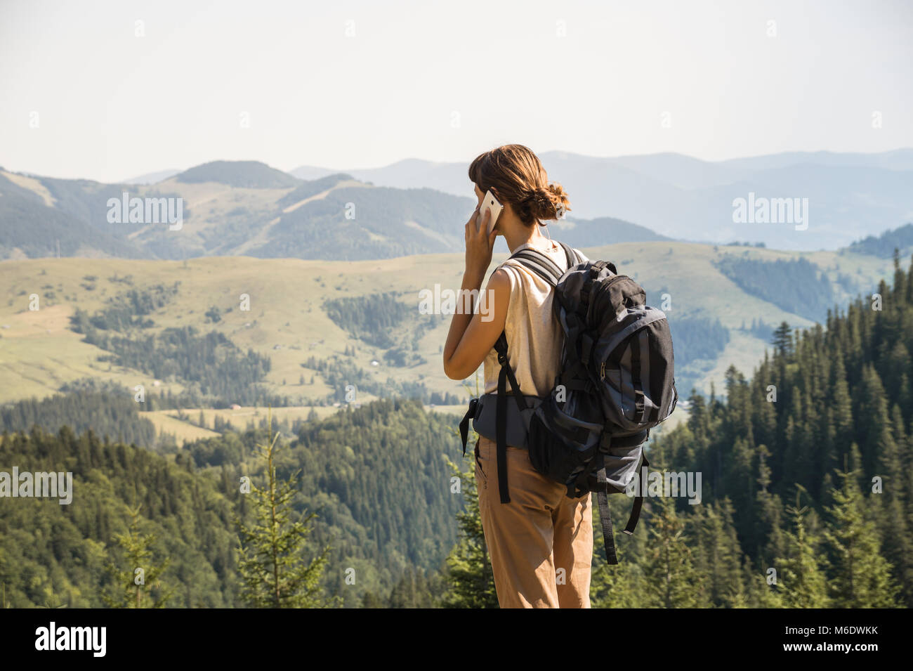 Girl with tourist rucksack on a long hiking walk talks on smartphone up in the hills - Stock Image