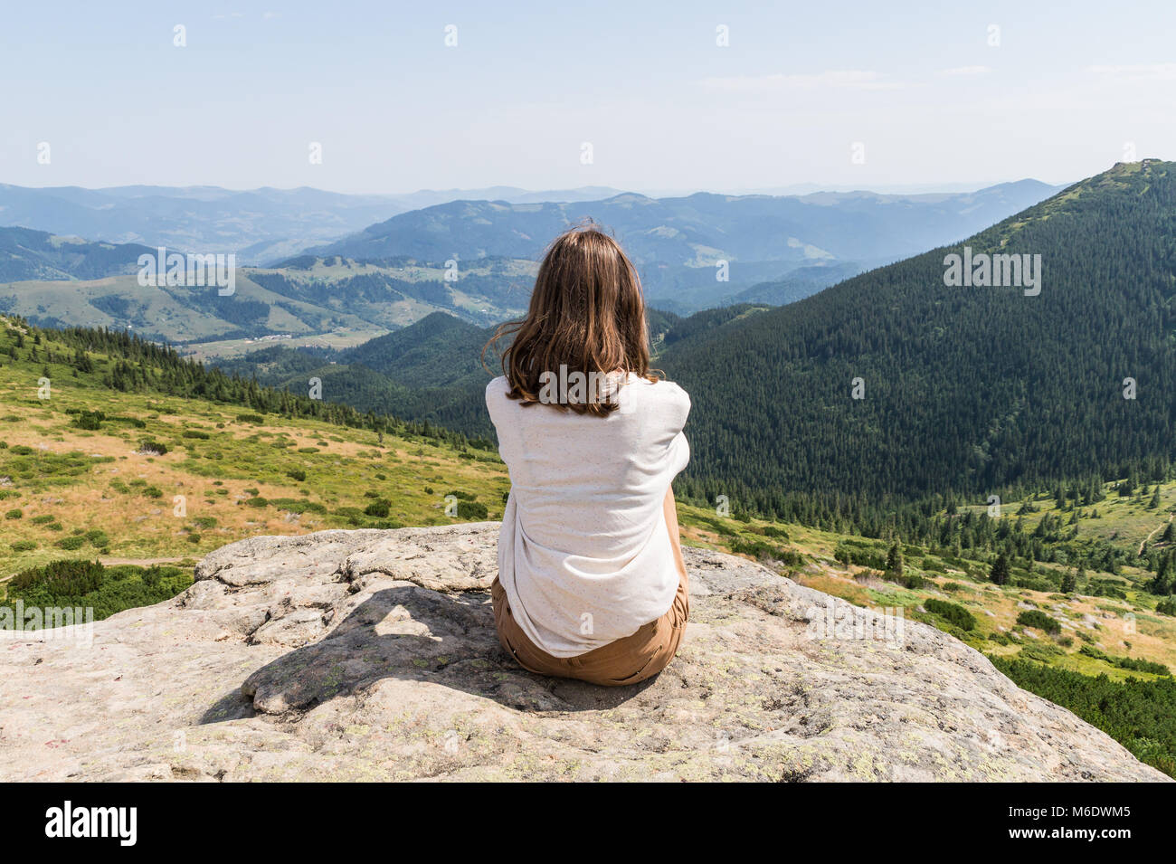 girl tourist enjoys gorgeous landscape scenery on hot sunny day - Stock Image