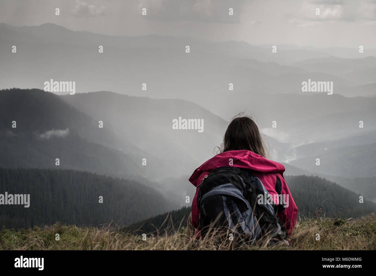 Young female hiker with backpack sits in grass on top of hill in ukrainian carpathians - Stock Image