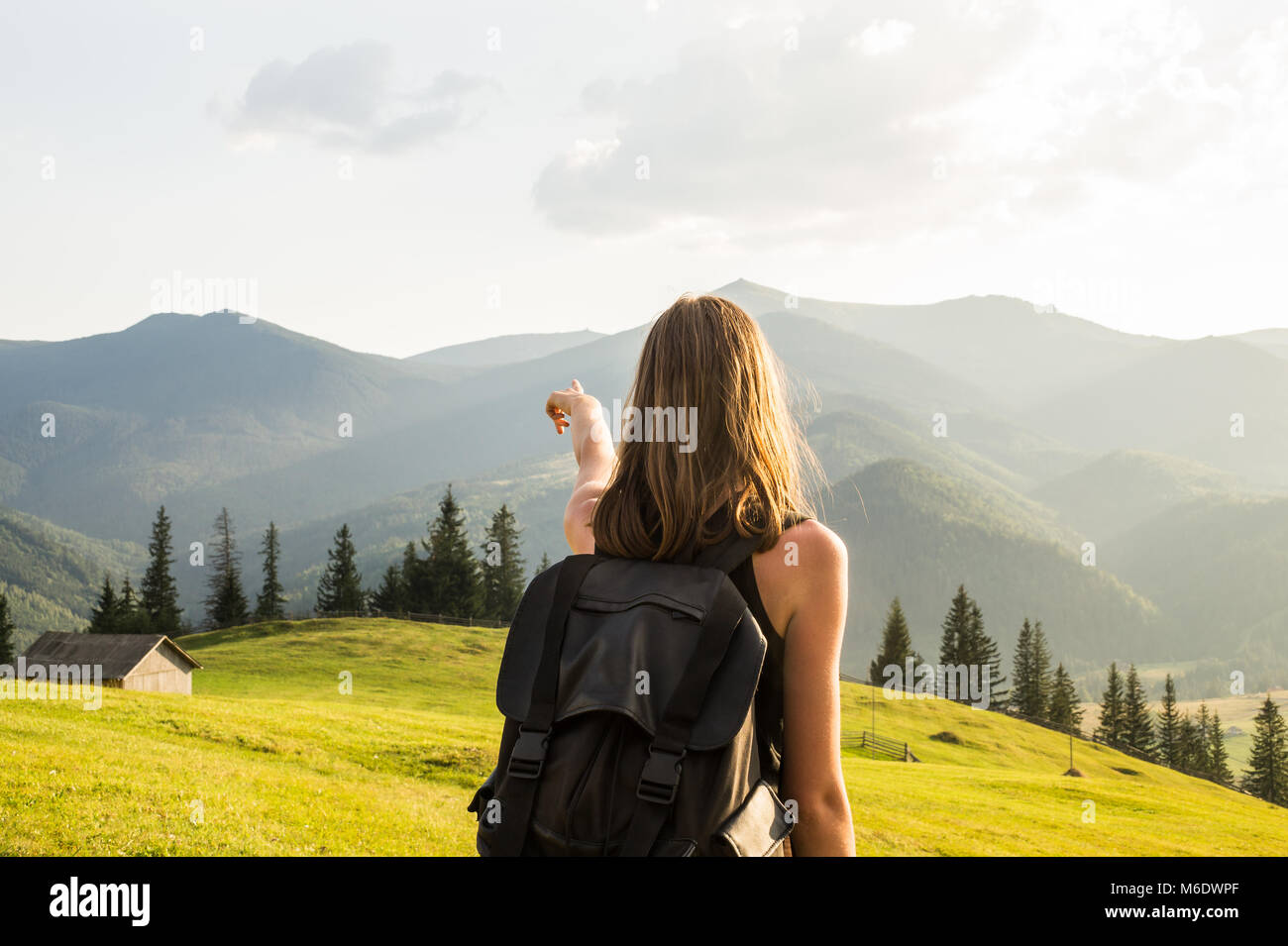 Young girl stands at hillside of ukrainian carpathian mountains and looks at distant mountain peaks - Stock Image