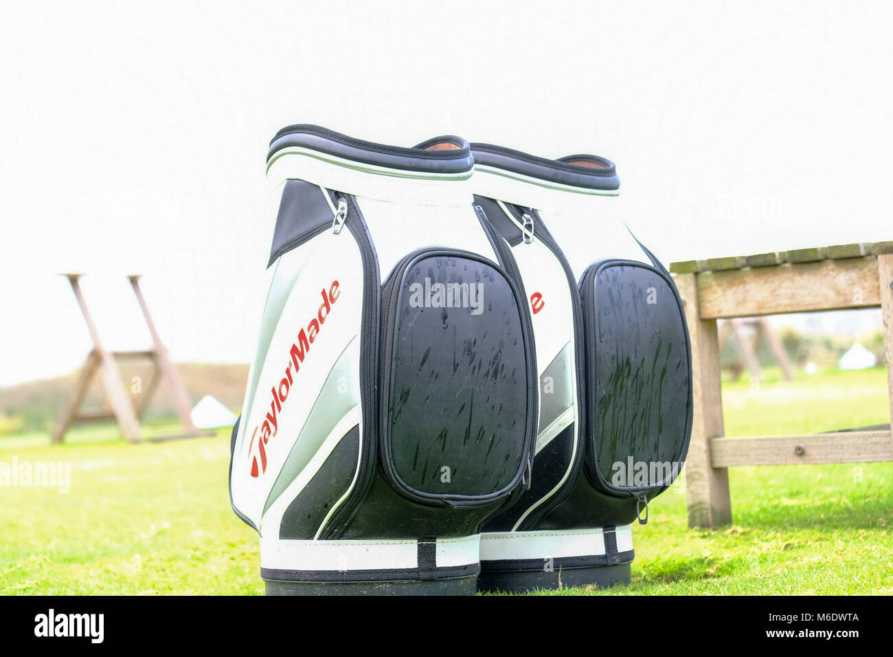 Couple of Taylormade Golf Bags outdoor in rainy weather - Stock Image