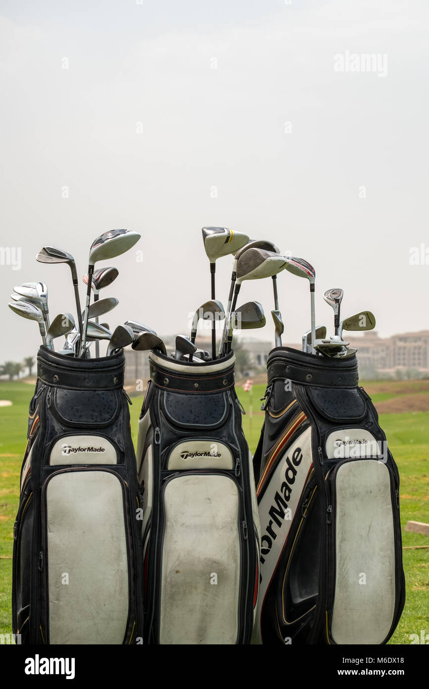 Three Golf bags full of Golf Clubs isolated against white sky - Stock Image