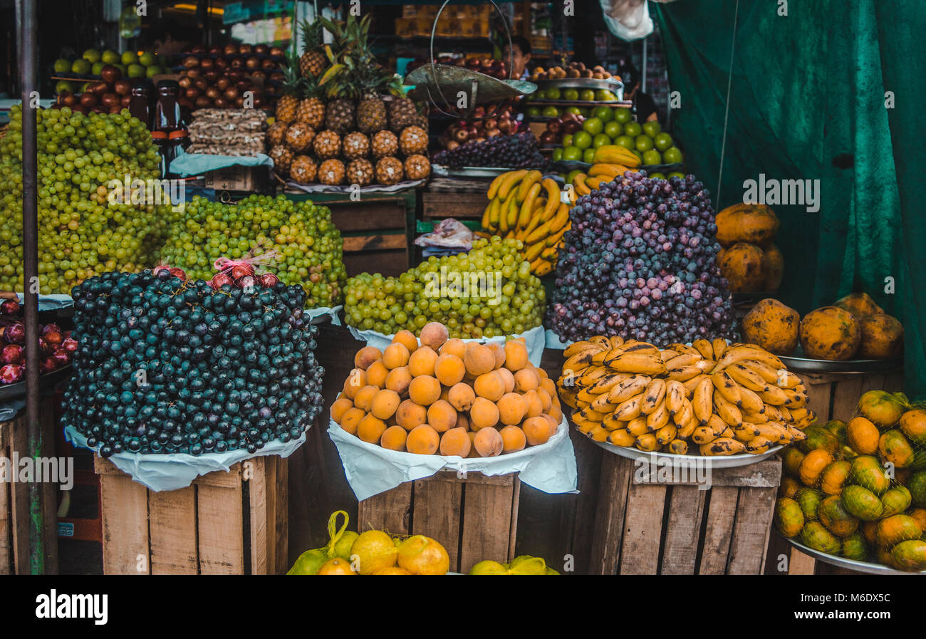 Fresh, organic fruit piled up in bowls in a packed street market stall in Bolivia - Stock Image