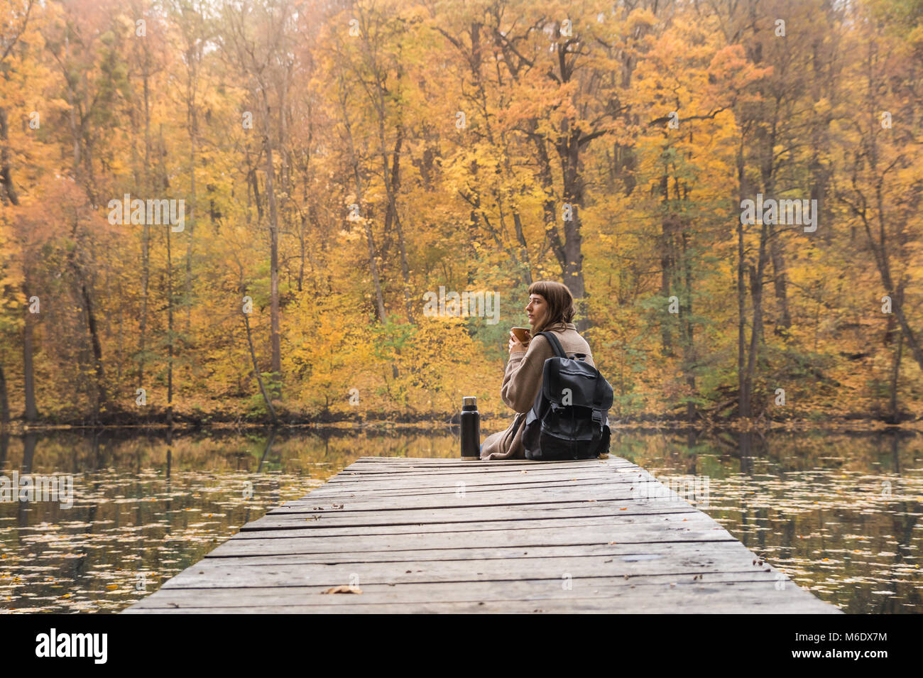 Young female hiker with backpack sits at riverbank, drinks coffee and looks at beautiful indian summer scenery - Stock Image