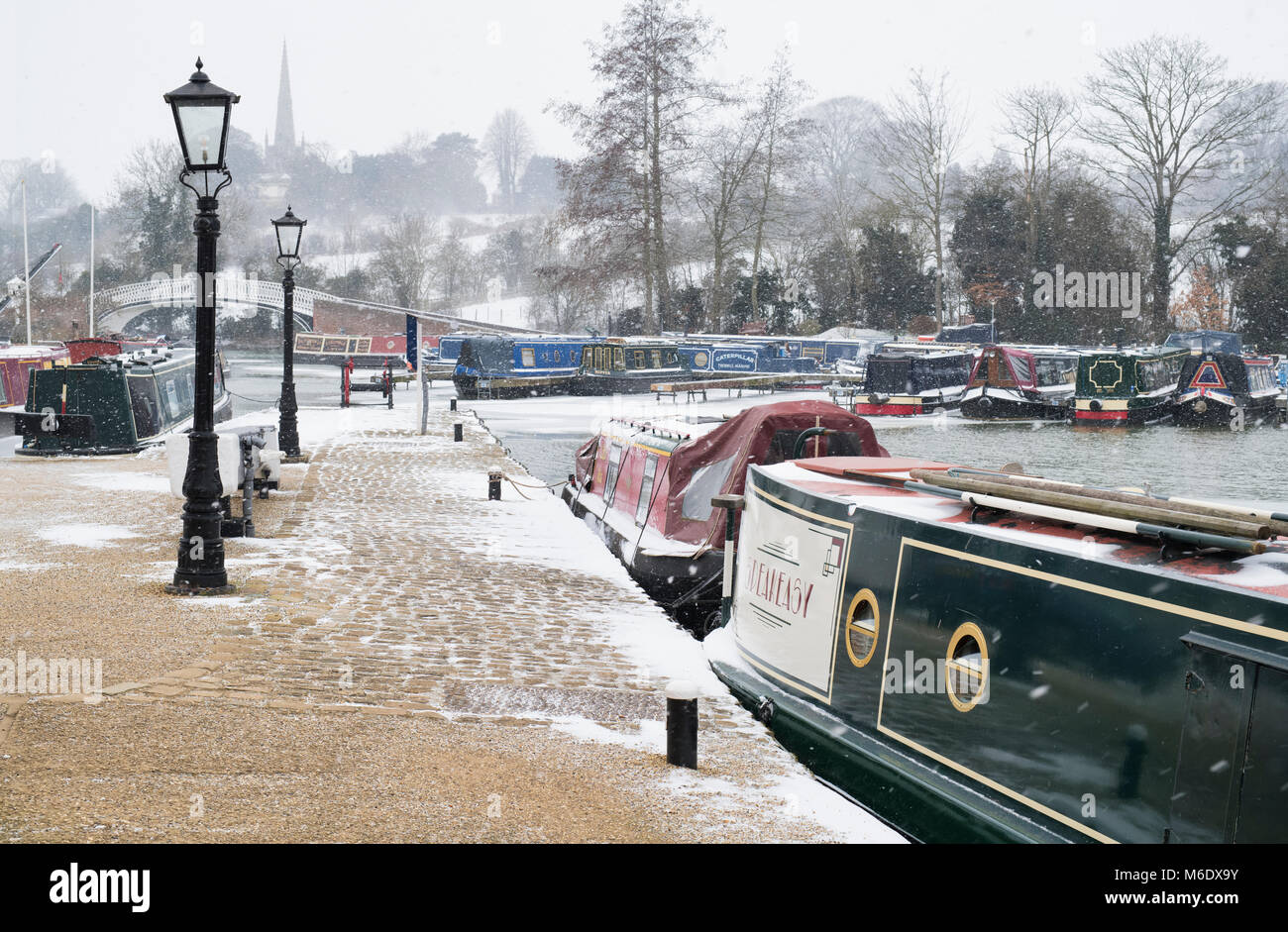 Canal boats in the snow in braunston marina in winter. The Wharf, Braunston, Northamptonshire, UK - Stock Image