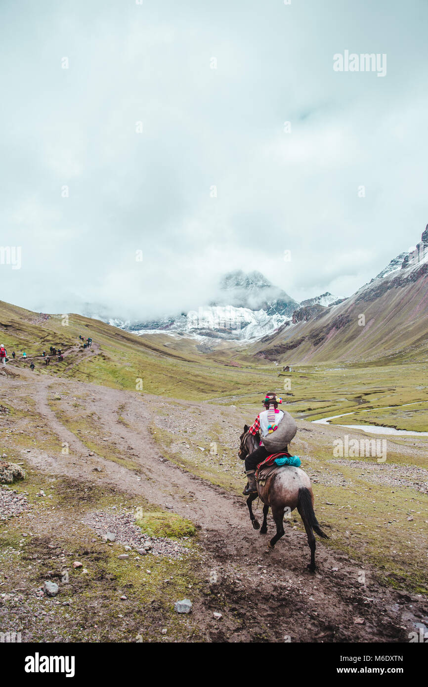 Traditional indigenous Quechua horseman rides his horse across the valleys of the Cusco region of Peru, next to - Stock Image