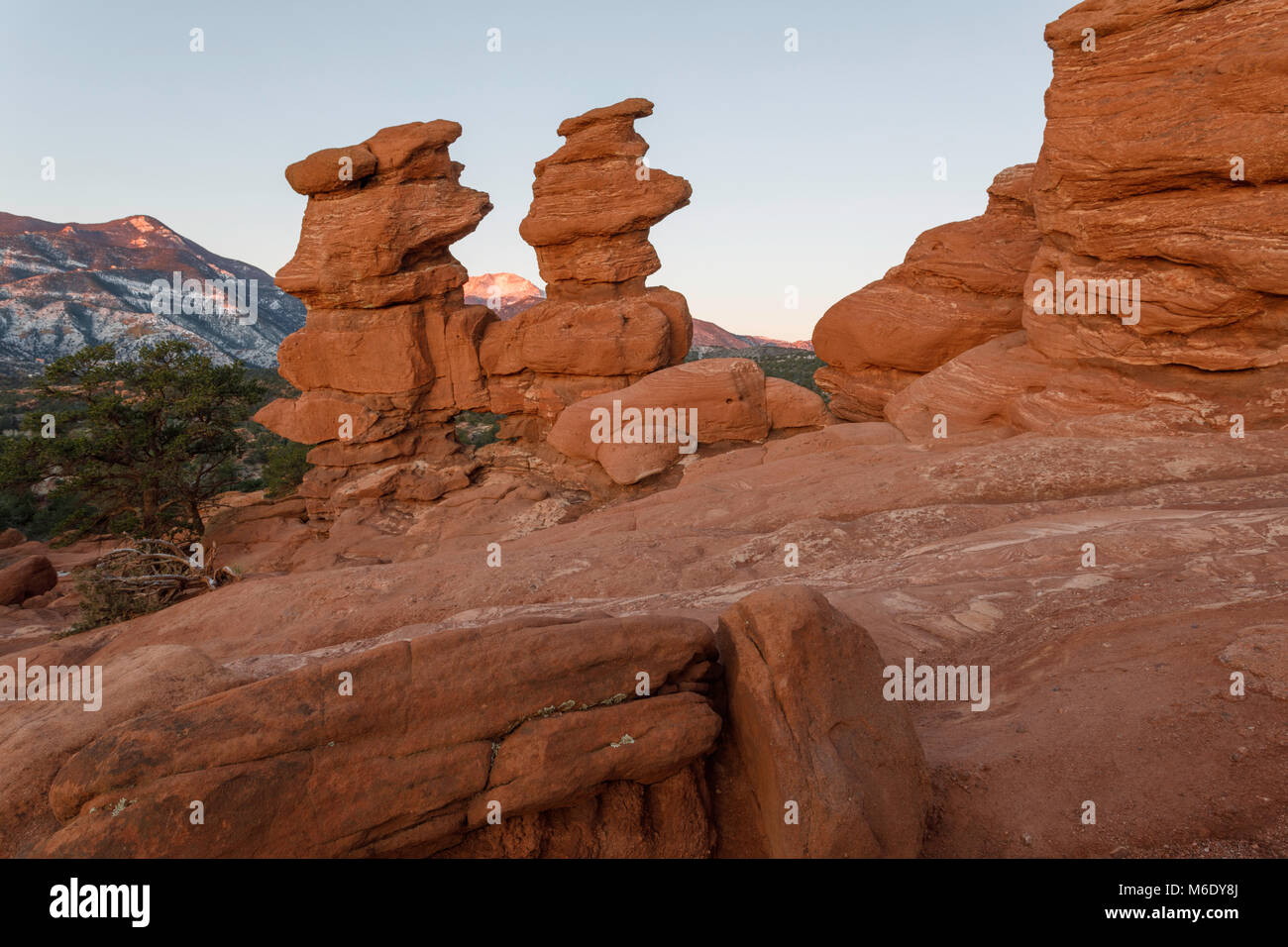 Pikes Peak is visible through the Siamese Twins rock formation at sunrise. - Stock Image