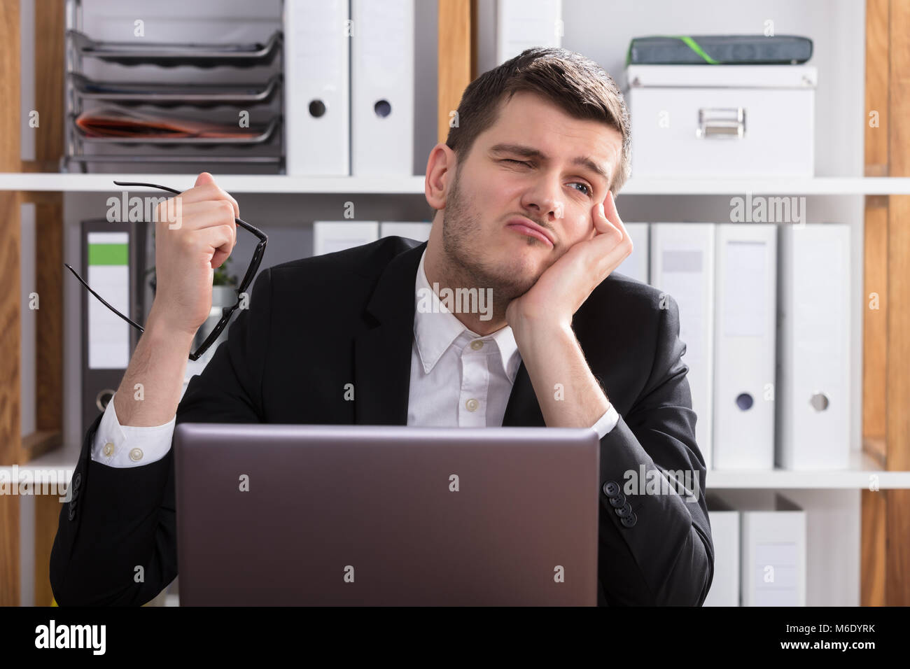 Contemplated Young Businessman Sitting Behind Laptop In Office - Stock Image
