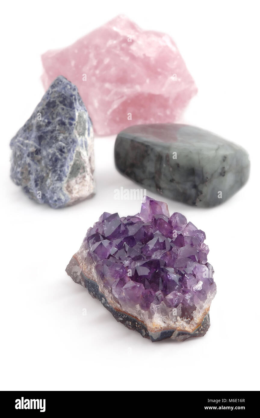 big crystal stones, gemstones, four different kinds, processed and unprocessed, on white background - Stock Image
