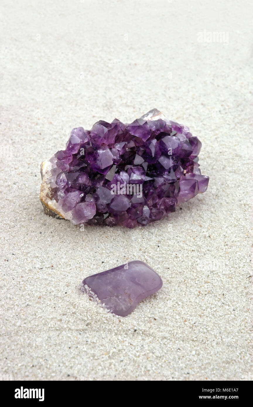 Amethyst, rough and smooth, processed and unprocessed, purple crystals on sand - Stock Image