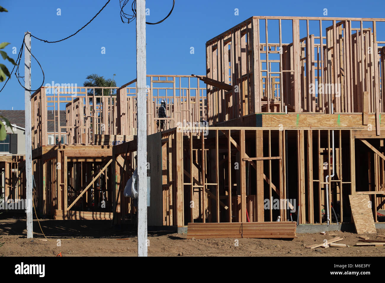 d6b04d9b Several new two-story homes under construction, just framed, with skeletal  walls built of 2 x 4 lumber; blue sky behind, power poles, on sunny day.
