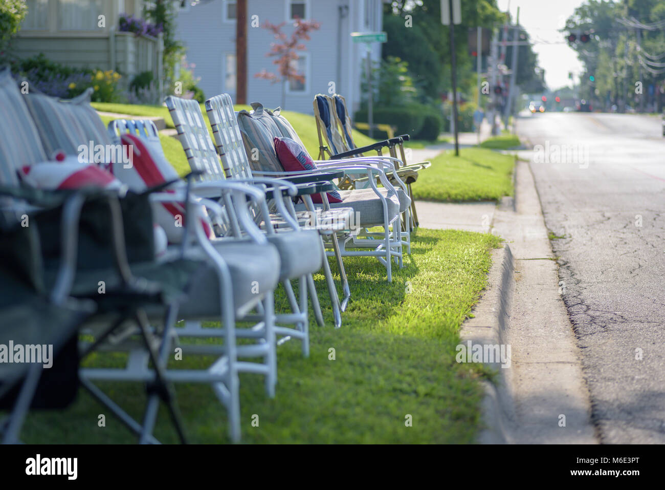 row of empty chairs staked out early along street for the annual fourth of July parade - Stock Image