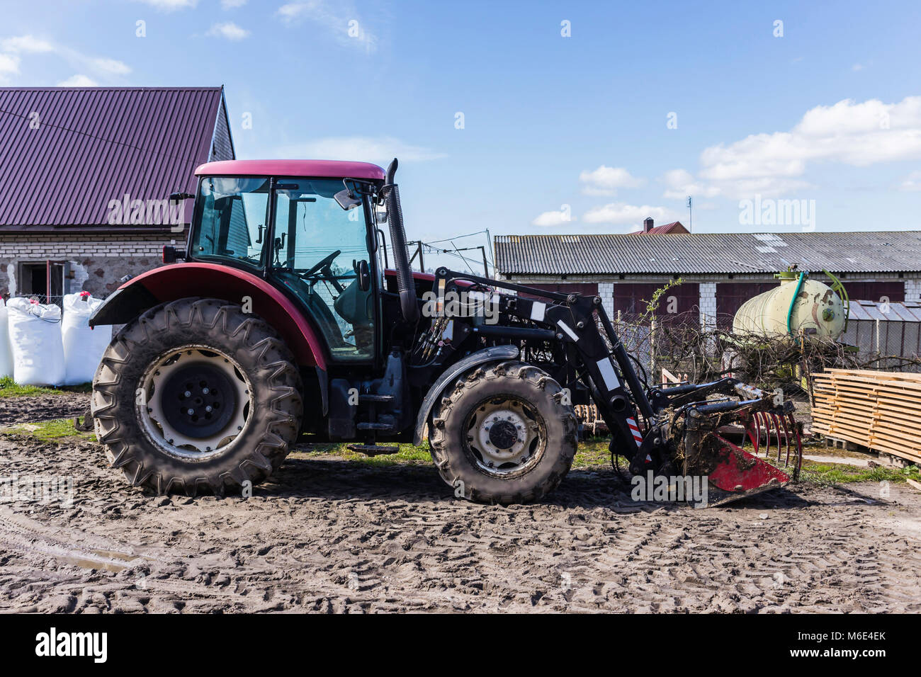 Agricultural machinery and equipment. Tractor with front loader for manure. The yard of a dairy farm. Podlaskie, - Stock Image