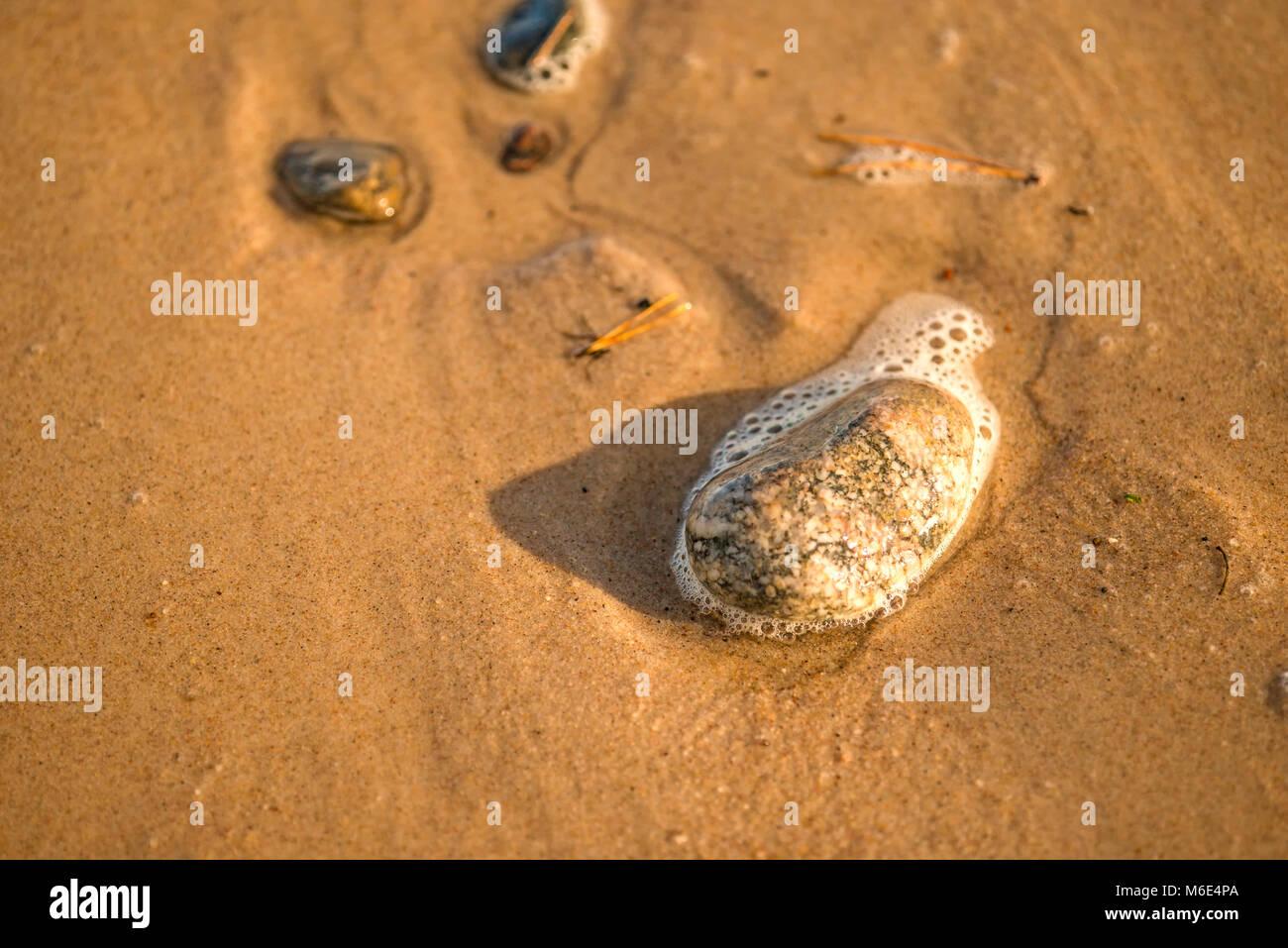 Sandstrand mit Schaum der Brandung - Stock Image
