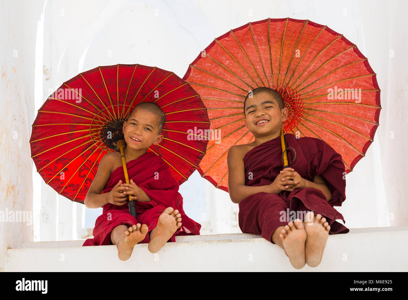 Young novice Buddhist monks holding parasols at Myatheindan Pagoda (also known as Hsinbyume Pagoda), Mingun, Myanmar - Stock Image