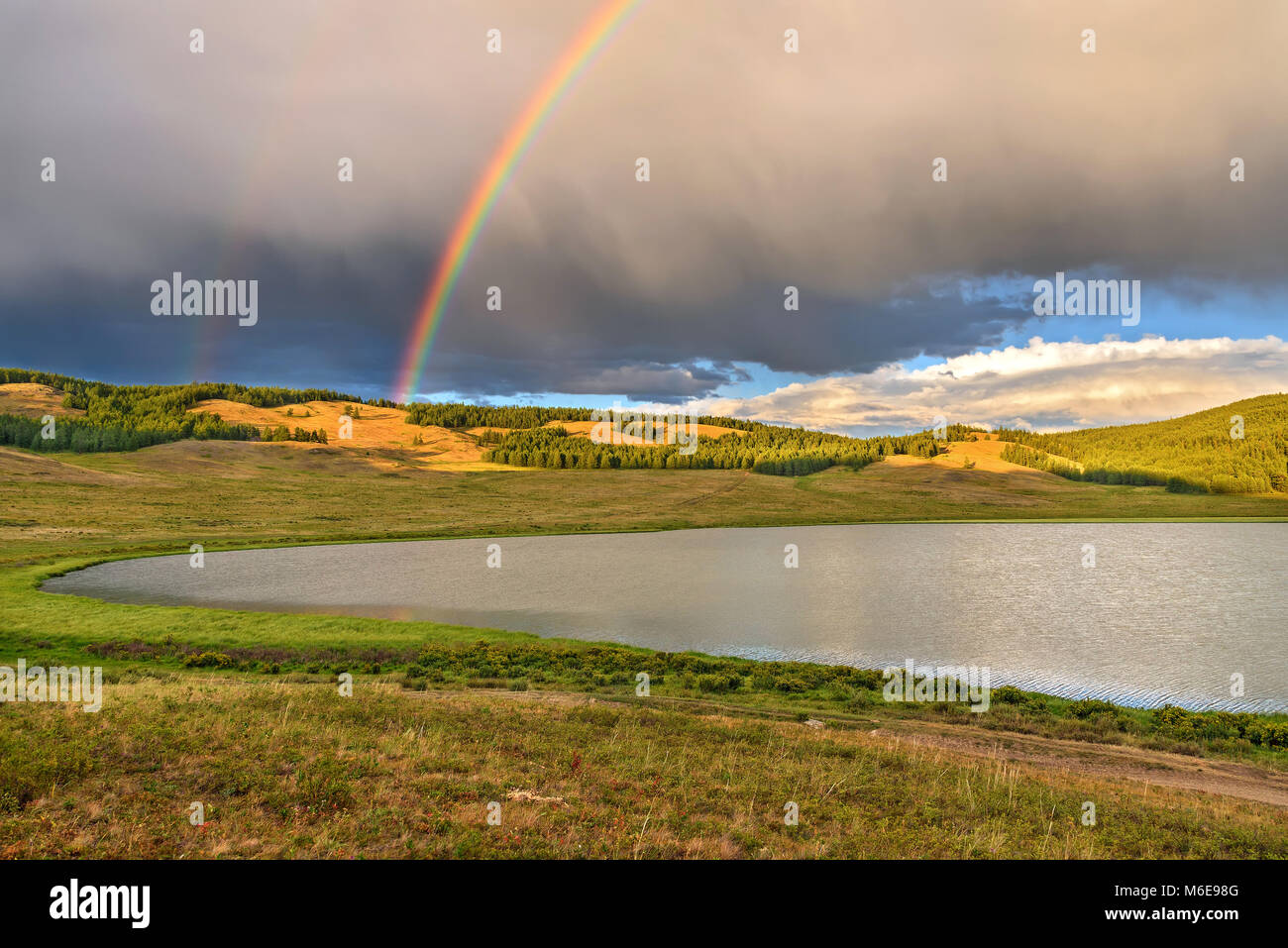 Bright colorful rainbow over the mountains, lake and forest after the rain against the blue sky with clouds in summer Stock Photo