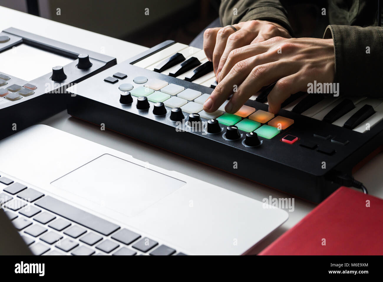 Recording electronic music track with portable midi keyboard on laptop computer in home studio - Stock Image