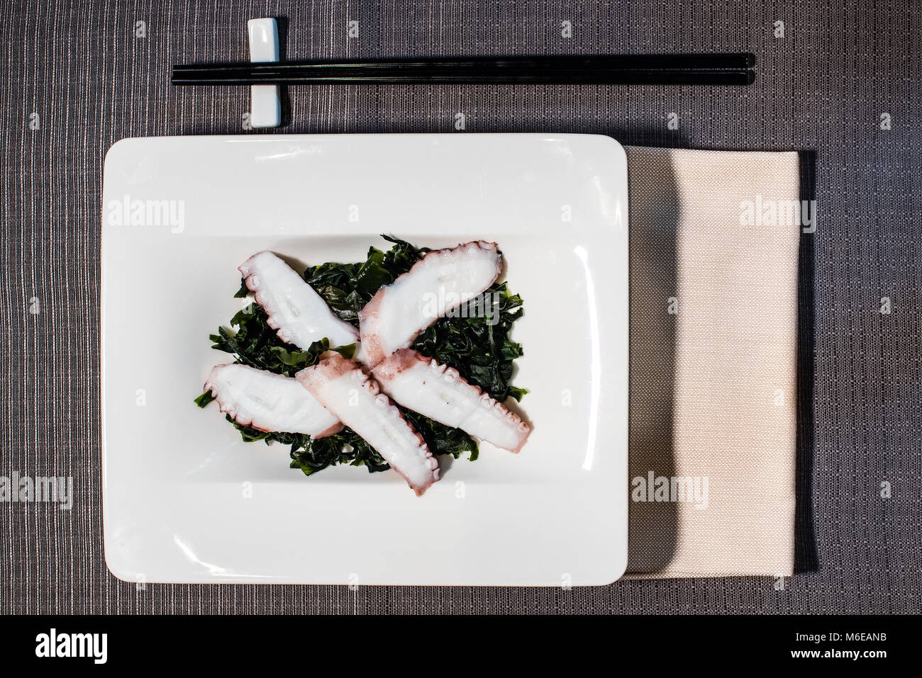 octopus fillets on bed of seaweeds seasoned with rice vinegar, served on a rectangular white plate with black chopsticks - Stock Image