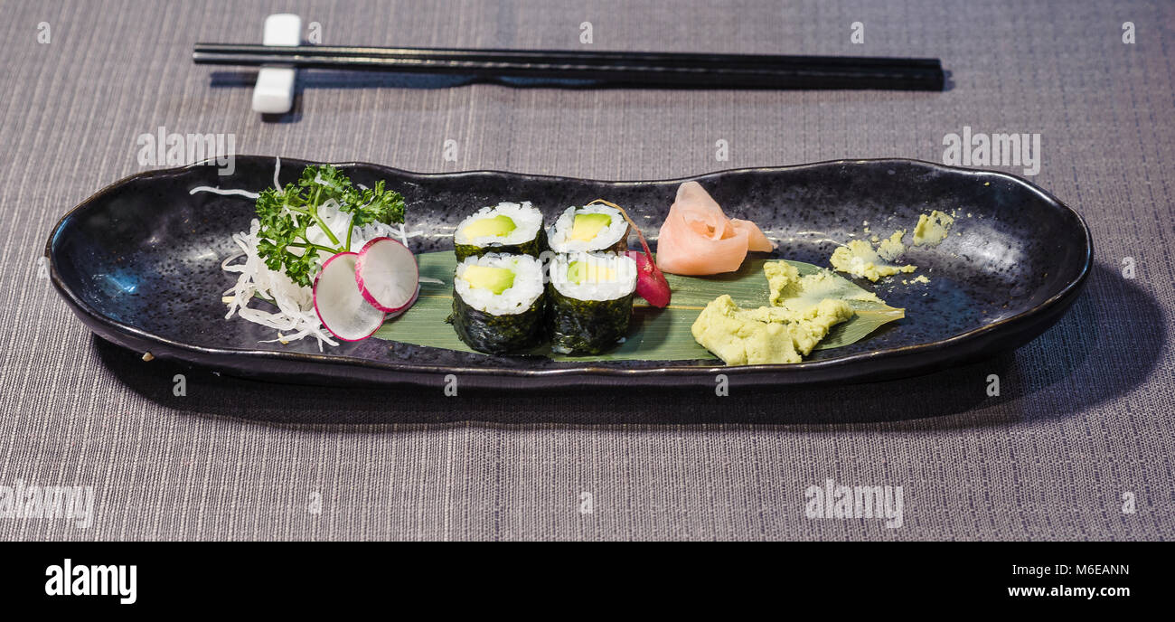 avocado sushi served on a bamboo leaf, with radishes and daikons julienne, ginger gari and horseradish wasabi, typical - Stock Image
