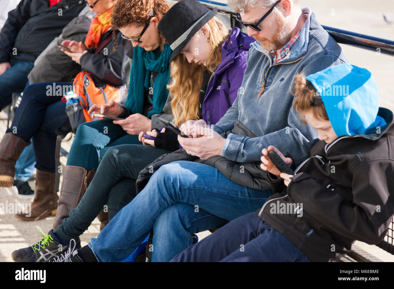 Family sitting on a bench, all of whom are simultaneously looking at their mobile phone / device / devices, texting - Stock Image