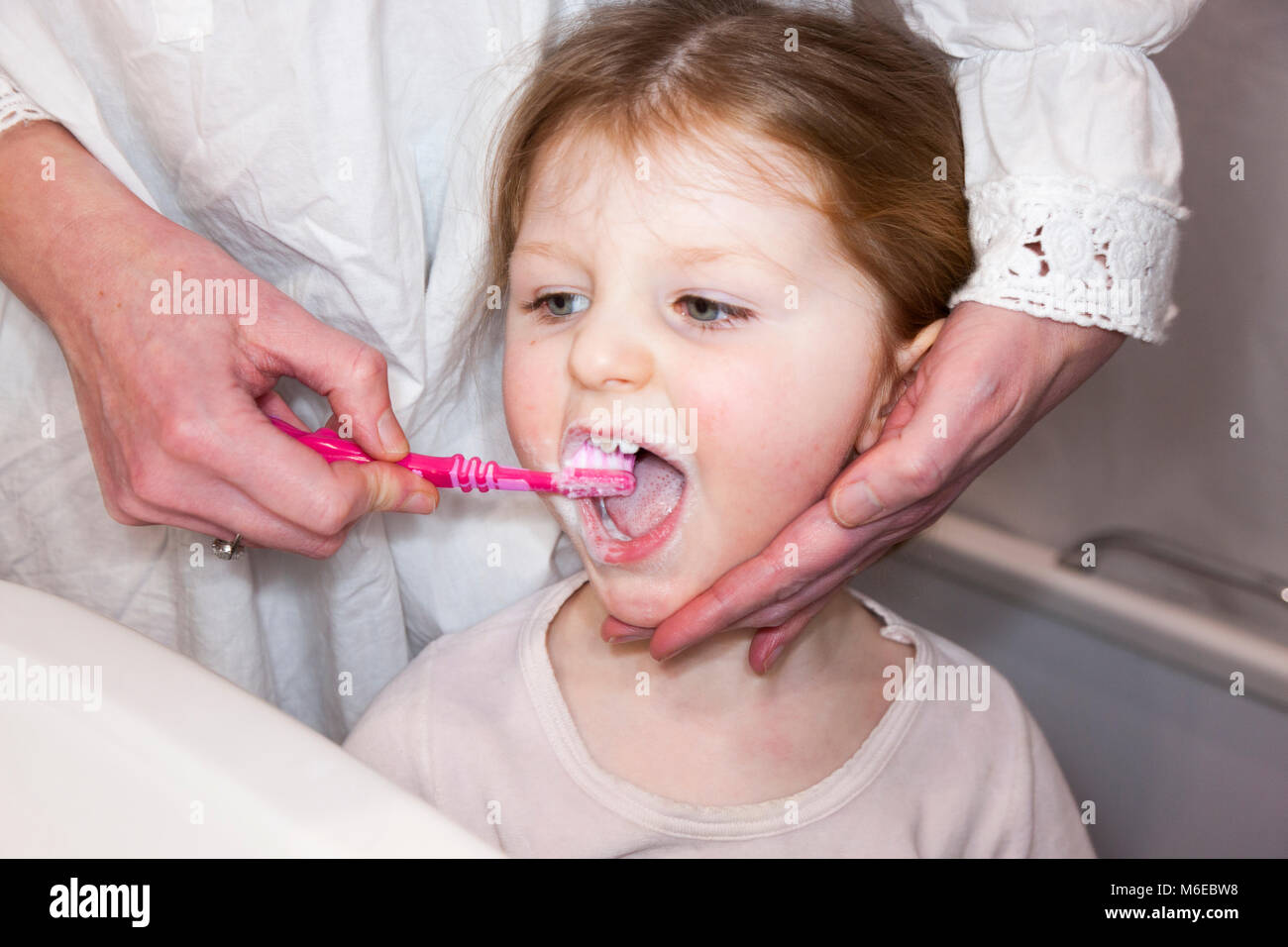 Three year old child / kid aged 3 years having her milk teeth brushed with a toothbrush / tooth brush - by her mother - Stock Image
