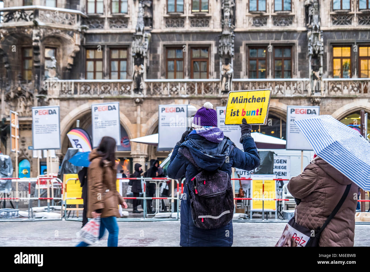MUNICH / GERMANY - FEBRUARY 15 2018: Lady is raising a sign against the PEGIDA demonstration, Translation: Munich - Stock Image