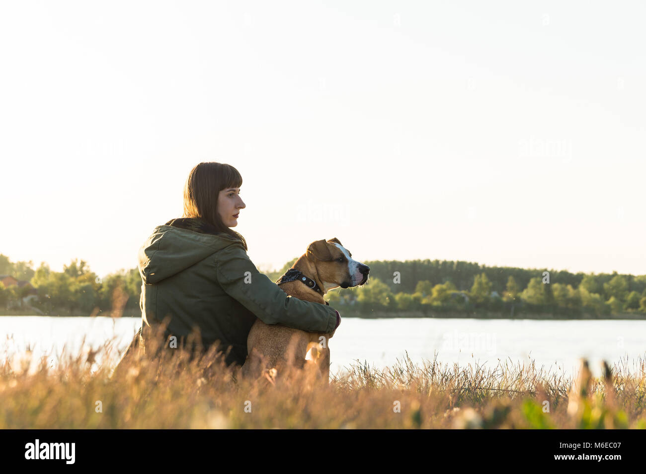 Dog owner and her pet sit at riverbank at sunset - Stock Image