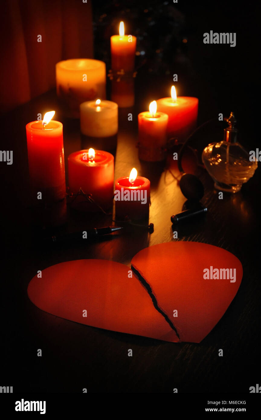 romantic love letter in shape of broken heart (teared paper)  with candles and old perfume bottle and pen. - Stock Image