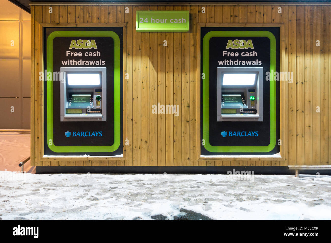 Cash machines in the side of an Asda supermarket, operated by Barclays bank, picture on a snowy night. - Stock Image
