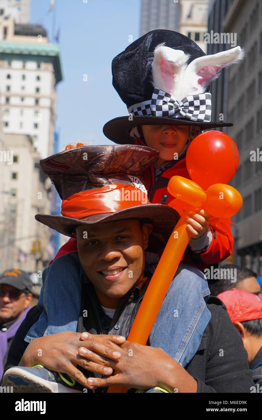 New York, New York, USA: Man carrying a child, both  wearing top hats, rabbit ears and an orange balloon at the - Stock Image