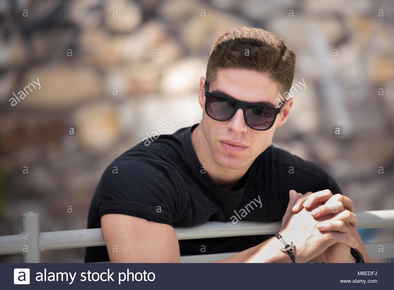 Man with sort ahir leaning lean on banister wear sunglasses looking away - Stock Image