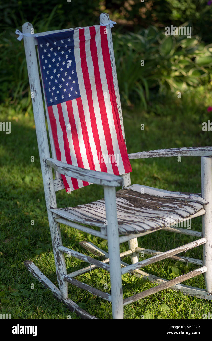 Closeup Of A Single Rustic White Painted Rocking Chair Sitting In Grass  With American Flag Hanging