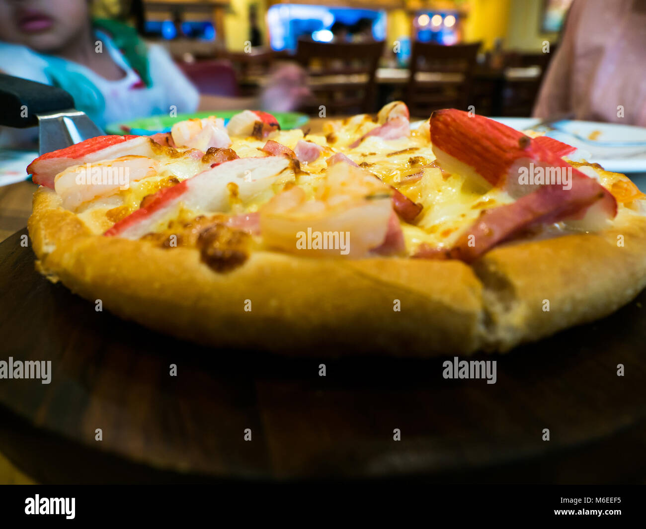 seafood pizza topping whit Crab, shrimp and ham On a wooden tray. The background is restaurant - Stock Image