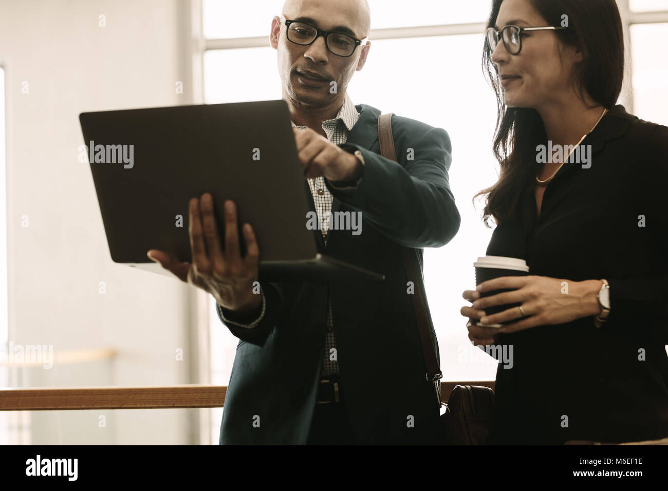 Businessman pointing at laptop and discussing something with coworker while standing at office. Business team working - Stock Image