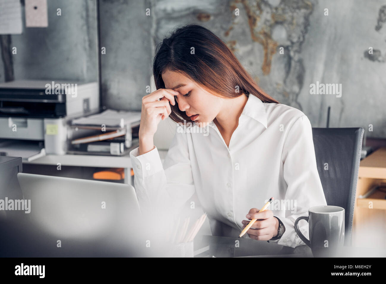 Frustrated Asian businesswoman cover her face with two hand and feel upset from work in front of laptop computer - Stock Image